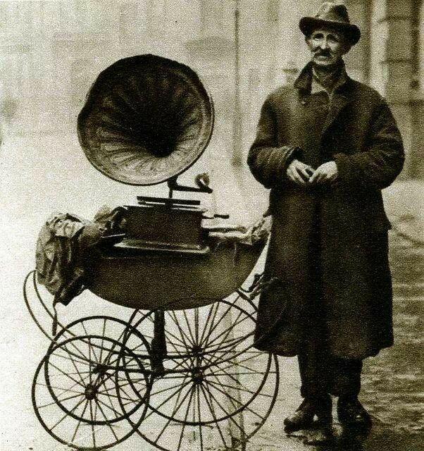 رجل بجانب مشغل الجراموفون المحمول. في عشرينيات القرن الماضي